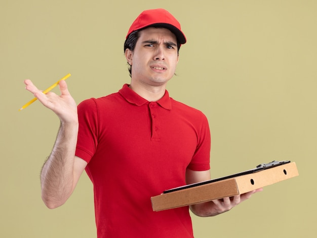 Fronsende jonge bezorger in rood uniform en pet met pizzapakket klembord en potlood kijkend naar voorkant geïsoleerd op olijfgroene muur