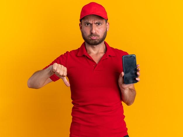 Fronsende jonge blanke bezorger in rood uniform en pet kijkend naar camera met mobiele telefoon en duim omlaag geïsoleerd op oranje muur