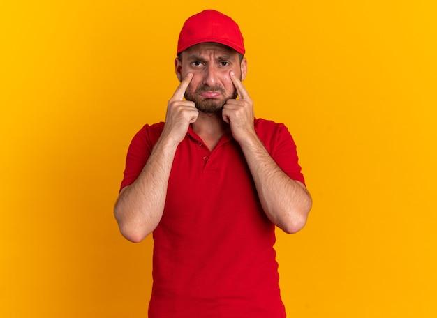 Fronsende jonge blanke bezorger in rood uniform en pet kijkend naar camera tuitende lippen houden vingers onder ogen geïsoleerd op oranje muur met kopieerruimte