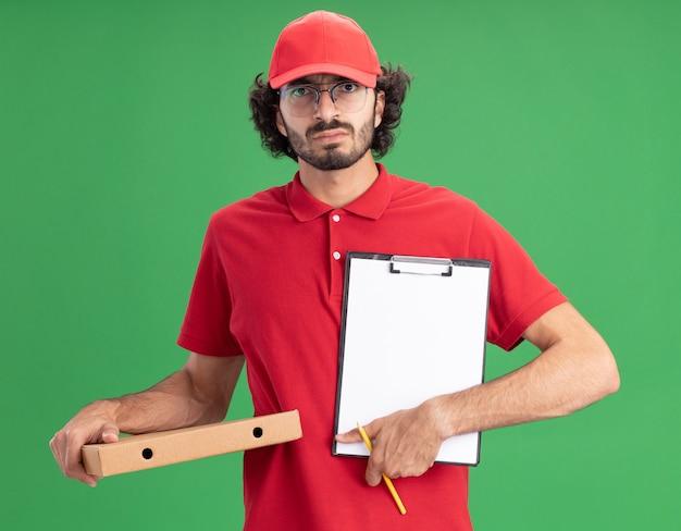 Fronsende jonge blanke bezorger in rood uniform en pet met bril met pizzapakket potlood met klembord naar camera geïsoleerd op groene muur