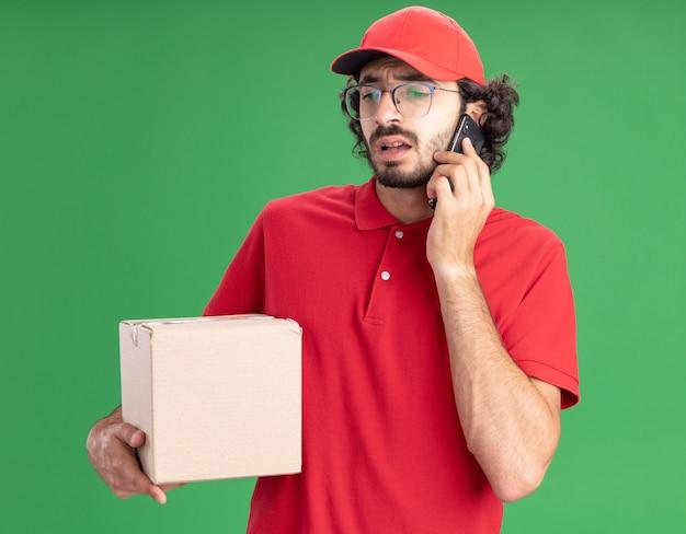Fronsende jonge blanke bezorger in rood uniform en pet met een bril die een kartonnen doos vasthoudt die aan de telefoon praat en neerkijkt op een groene muur