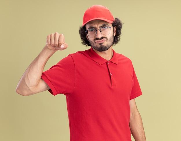 Fronsende jonge blanke bezorger in rood uniform en pet met een bril die een kloppend gebaar doet geïsoleerd op olijfgroene muur