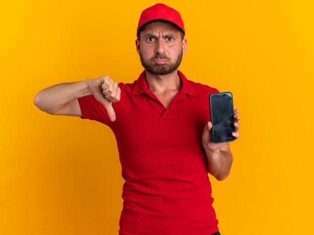 Fronsende jonge blanke bezorger in rood uniform en pet met mobiele telefoon en duim omlaag