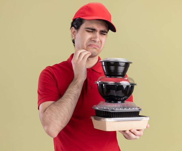 Fronsende jonge blanke bezorger in rood uniform en pet met voedselcontainers en papieren voedselpakket kijkend naar hen terwijl ze de kin raken