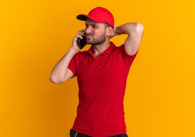 Fronsende jonge blanke bezorger in rood uniform en pet pratend aan de telefoon terwijl hij de hand achter het hoofd houdt en naar de zijkant kijkt die op een oranje muur is geïsoleerd