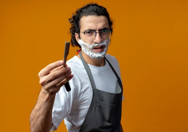 Fronsende jonge blanke mannelijke kapper met een bril en een golvende haarband in uniform die een scheermes met scheerschuim op zijn gezicht uitrekt