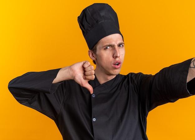 Fronsende jonge blonde mannelijke kok in uniform van de chef-kok en pet kijken camera hand uitstrekken naar camera met duim naar beneden geïsoleerd op oranje muur