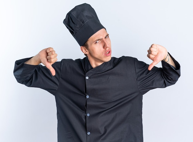 Fronsende jonge blonde mannelijke kok in uniform van de chef-kok en pet kijken naar camera met duimen naar beneden geïsoleerd op een witte muur