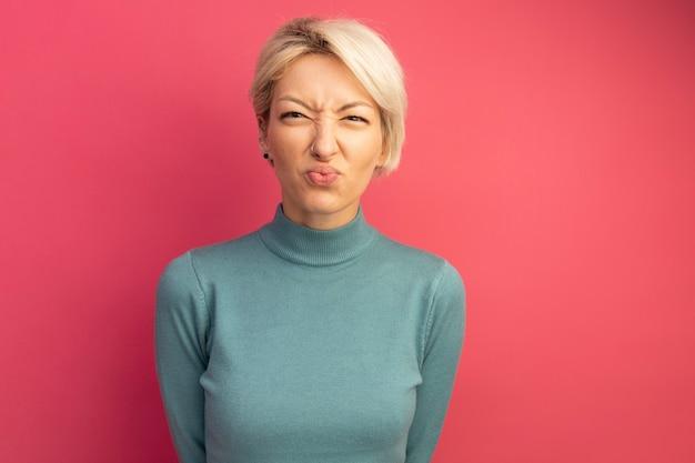 Fronsende jonge blonde vrouw die naar de voorste lippen kijkt die op een roze muur met kopieerruimte wordt geïsoleerd