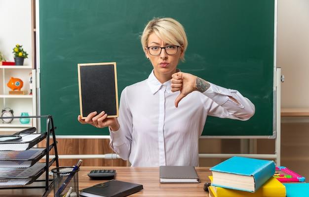 Fronsende jonge blonde vrouwelijke leraar met een bril die aan het bureau zit met schoolhulpmiddelen in de klas met mini-bord en duim omlaag