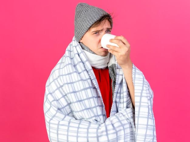 Fronsende jonge knappe blonde zieke man met winter muts en sjaal gewikkeld in een plaid op zoek recht drinkend kopje thee geïsoleerd op roze muur