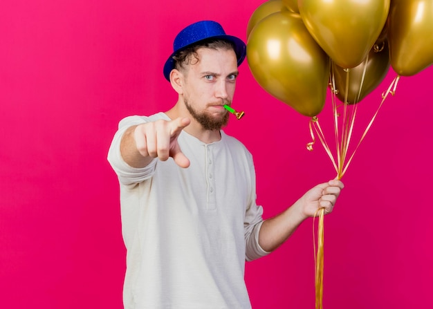 Fronsende jonge knappe slavische feestmens met feestmuts met ballonnen en partijblazer kijken en wijzend naar voorzijde geïsoleerd op roze muur met kopie ruimte