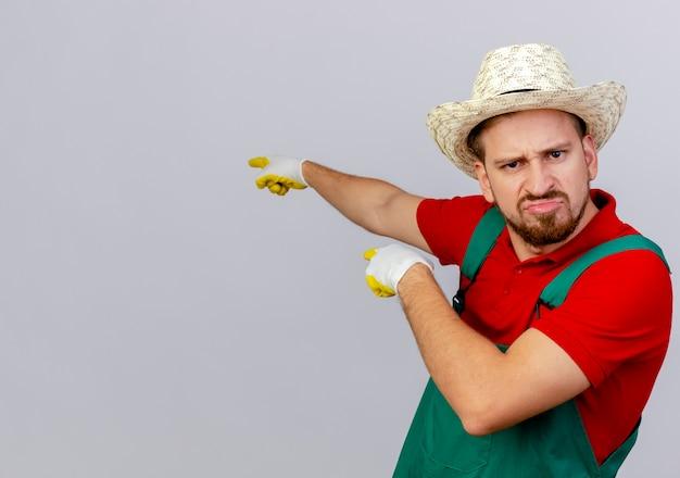 Fronsende jonge knappe slavische tuinman in uniform met tuinhandschoenen en hoed op zoek wijzend achter geïsoleerd