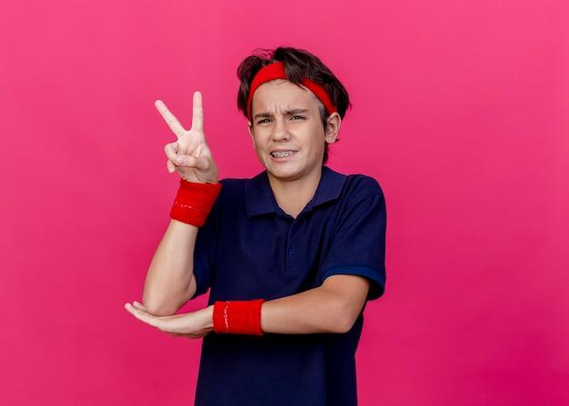 Fronsende jonge knappe sportieve jongen die hoofdband en polsbandjes met beugels draagt, hand onder de elleboog zetten, naar voren kijken, vredesteken doen geïsoleerd op karmozijnrode muur