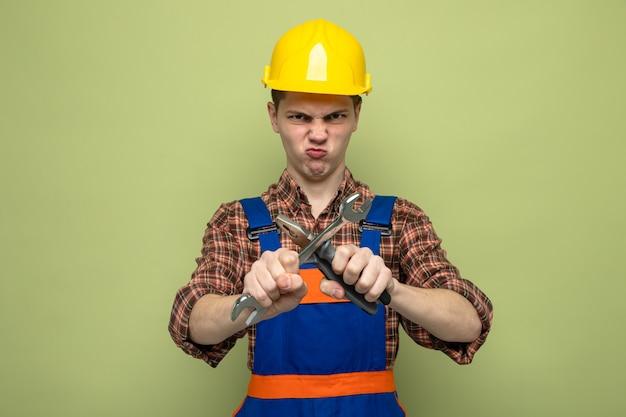 Fronsende jonge mannelijke bouwer die uniform vasthoudt en steeksleutel met een tang kruist