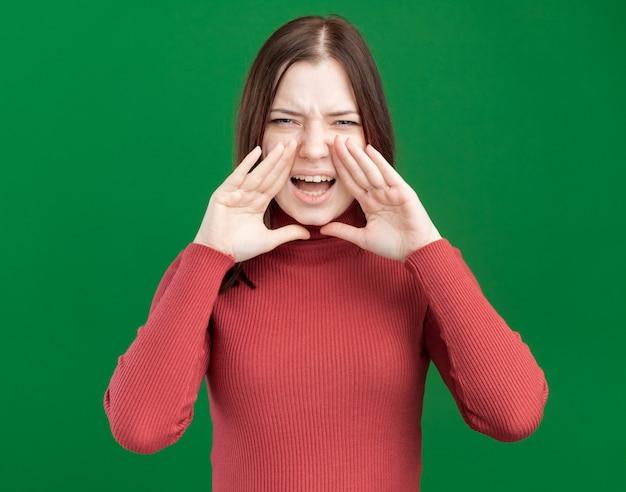 Fronsende jonge mooie vrouw die hand in de buurt van de mond houdt en naar de voorkant kijkt en hardop roept naar iemand die op een groene muur is geïsoleerd