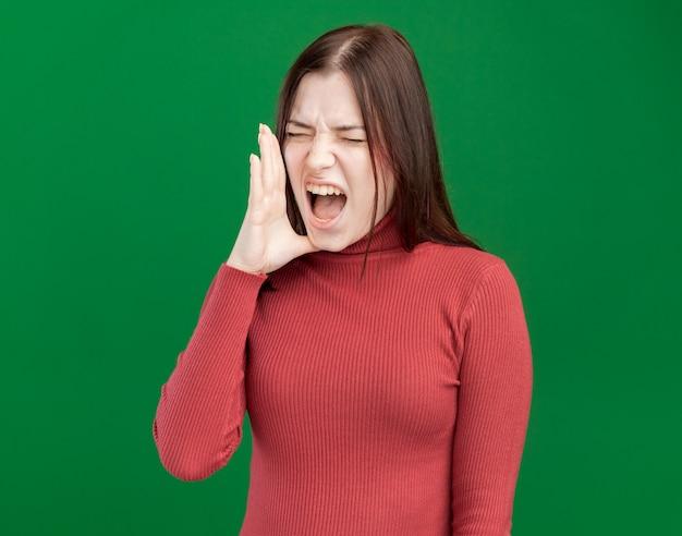 Fronsende jonge mooie vrouw die hand in de buurt van mond houdt en hardop roept naar iemand met gesloten ogen geïsoleerd op groene muur green