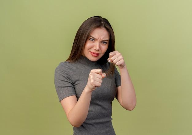 Fronsende jonge mooie vrouw doet boksgebaar vooraan op olijfgroene muur