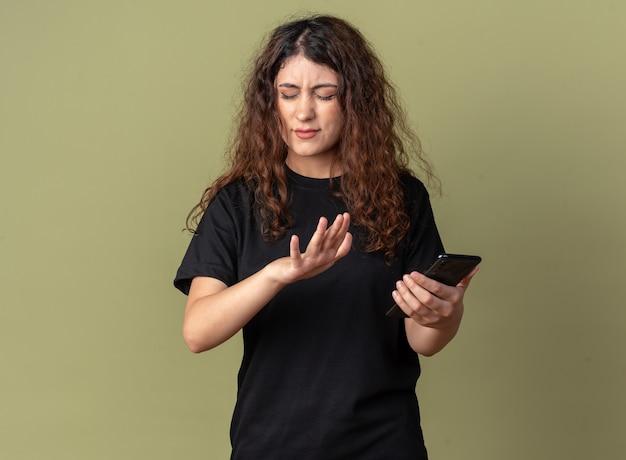 Fronsende jonge mooie vrouw met mobiele telefoon die weigeringsgebaar doet met gesloten ogen geïsoleerd op olijfgroene muur met kopieerruimte