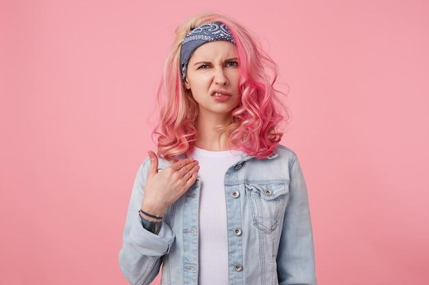 Fronsende jonge schattige dame met roze haar, accepteert agressief kritiek en kijkt ontevreden, wijst naar zichzelf en kijkt met walging, staat op.