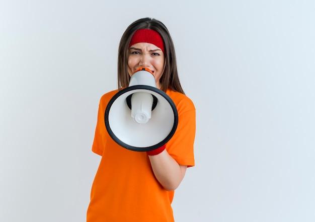 Fronsende jonge sportieve vrouw die hoofdband en polsbandjes draagt die pratend door geïsoleerde spreker kijken