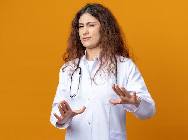 Fronsende jonge vrouwelijke arts die medische mantel en stethoscoop draagt die weigeringsgebaar doet met één oog gesloten geïsoleerd op oranje muur met kopieerruimte