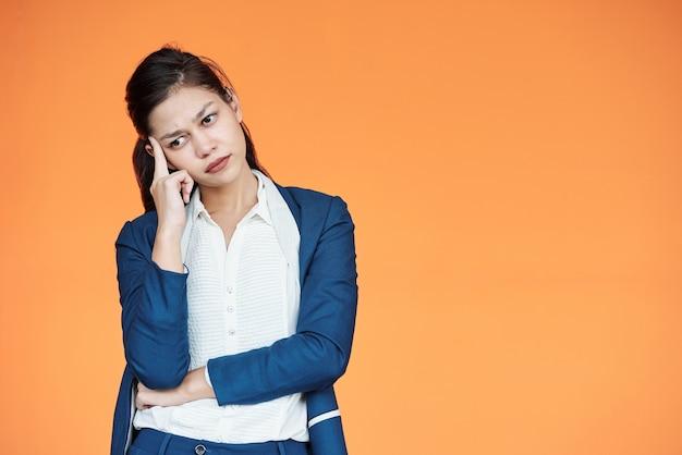 Fronsende jonge vrouwelijke ondernemer die denkt hoe ze zaken moet doen in tijden van coronaviruscrisis