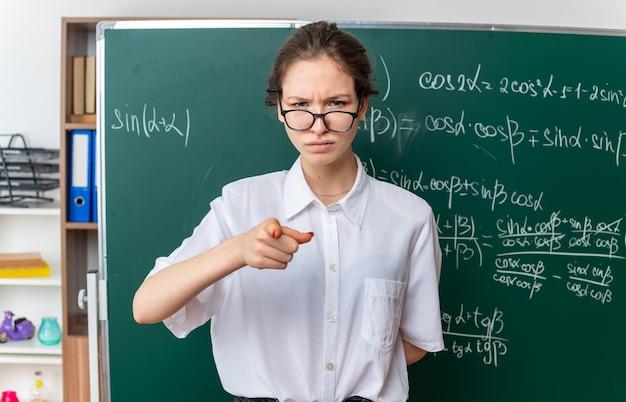 Fronsende jonge vrouwelijke wiskundeleraar met een bril die voor het bord staat en de hand achter de rug houdt kijkend en wijzend naar voren in de klas