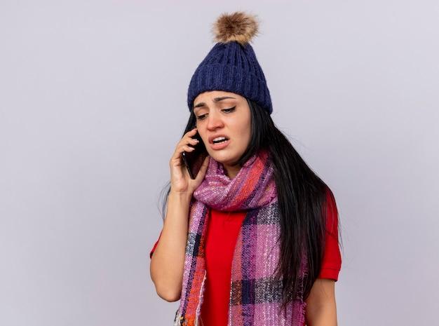 Fronsende jonge zieke vrouw die de wintermuts en sjaal draagt die op telefoon spreekt die neer geïsoleerd op witte muur kijkt