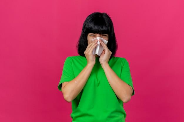 Fronsende jonge zieke vrouw die voorzijde afvegende neus met servet bekijkt dat op roze muur wordt geïsoleerd