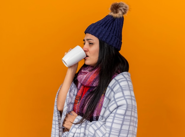 Fronsende jonge zieke vrouw met muts en sjaal gewikkeld in plaid staande in profiel te bekijken kopje thee drinken op zoek recht geïsoleerd op oranje muur