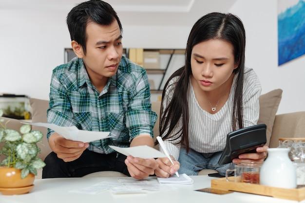 Fronsende jongeman die een energierekening of een winkelbon toont aan zijn vriendin die de financiën beheert