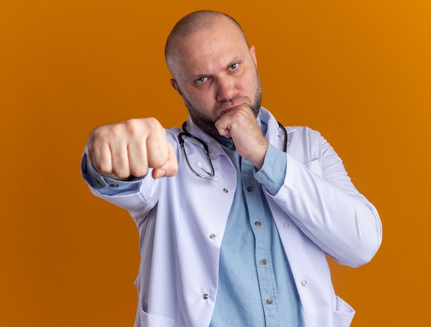 Fronsende mannelijke arts van middelbare leeftijd met een medisch gewaad en een stethoscoop die een boksgebaar doet