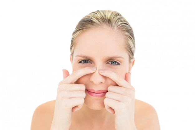 Fronsende verse blonde vrouw die op haar neus drukt