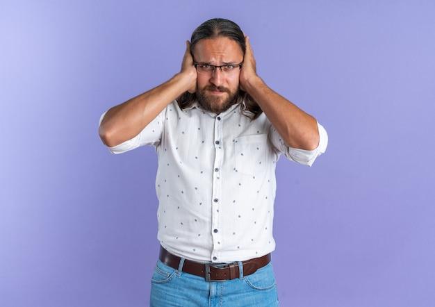 Fronsende volwassen knappe man met een bril die oren bedekt met handen