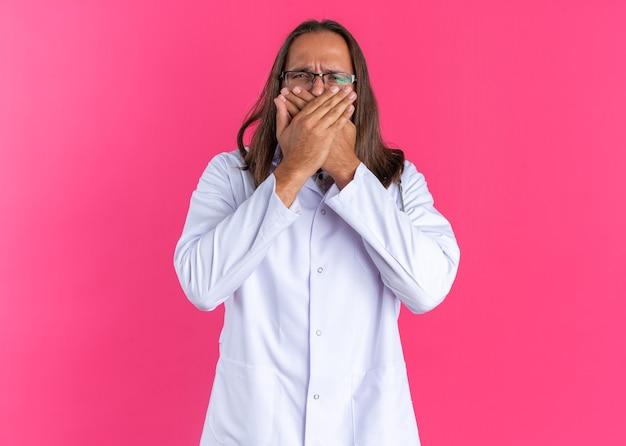 Fronsende volwassen mannelijke arts die medische mantel en stethoscoop draagt met een bril die de handen op de mond houdt en naar de camera kijkt die op een roze muur is geïsoleerd