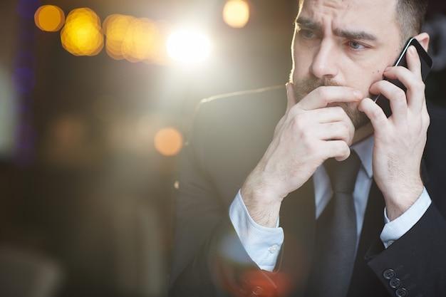 Fronsende zakenman die door smartphone spreekt