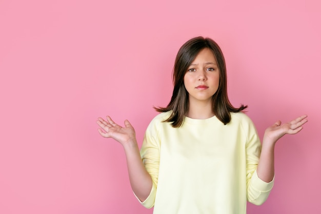 Fronst het tiener donkerbruine meisje op een roze achtergrond
