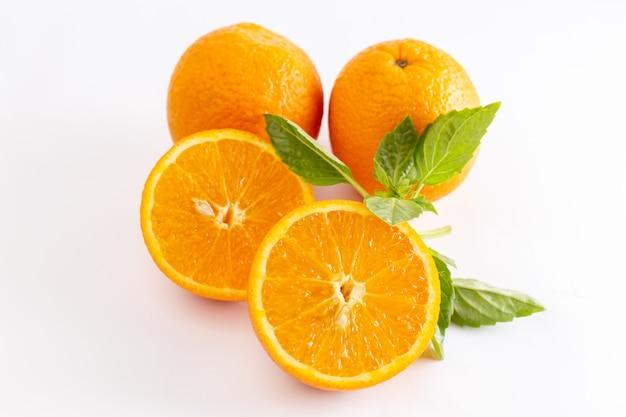 Front close view verse hele sinaasappelen sappig en zuur op het witte oppervlak