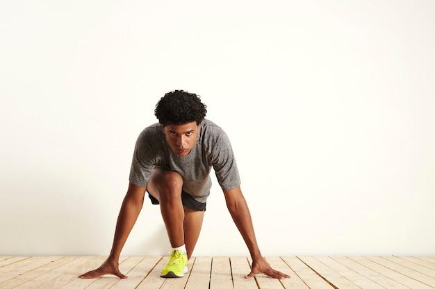 Front shot van een gefocuste fit runner die grijs, zwart en geel draagt in de uitgangspositie, klaar om te beginnen met rennen op wit