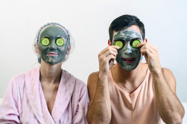 Frontaal portret van een echtpaar met kleimaskers op zijn gezicht en komkommers voor hem. spa thuis. huidverzorging