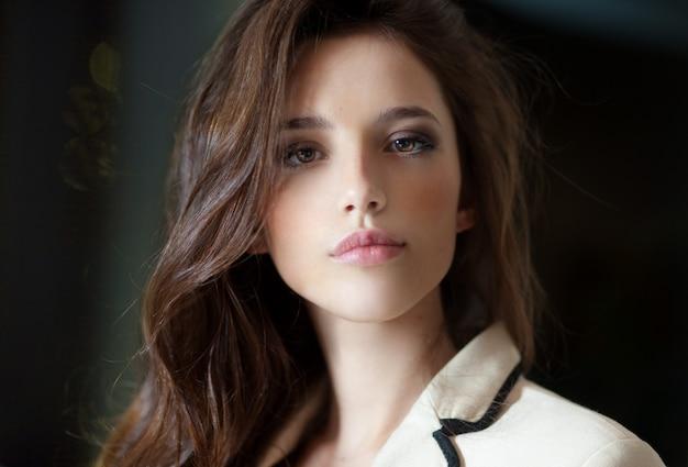 Frontaal portret van een jonge vrouw met lang haar, gekleed in een delicaat pak, kijkend naar de camera.