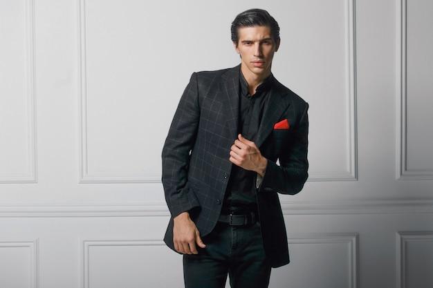 Frontaal portret van zelfverzekerde jonge man in zwart elegant pak met rode zijden sjaal in zak, op witte achtergrond.