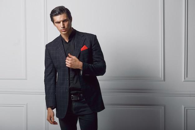 Frontale portret van zelfverzekerde jonge man in zwart stijlvol pak met rode zijden sjaal in zak, op witte achtergrond. kopieer ruimte.
