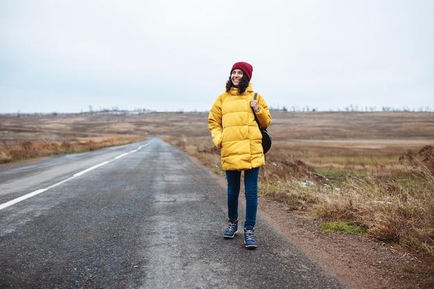 Frontview van een vrouwelijke toerist met een rugzak die een geel jasje en een rode hoed draagt, loopt op de weg.