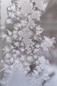 Frosty patroon gemaakt van puntige sneeuwvlokken op winter vensterglas.