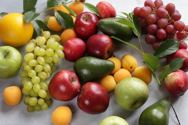 Fruit achtergrond met appels, druiven, abrikozen, perziken en avocado