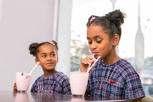 Fruit cocktail. krullend donkerharig schoolmeisje dat haar melk en fruitcocktail drinkt die dichtbij haar zuster zit