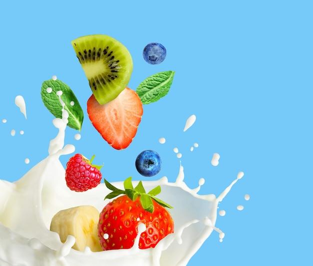 Fruit en bessen vallen in melk en spatten geïsoleerd op blauwe achtergrond