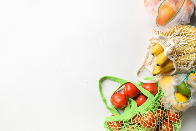Fruit en citroen in herbruikbare milieuvriendelijke netzakken op roze achtergrond. zero waste shopping.